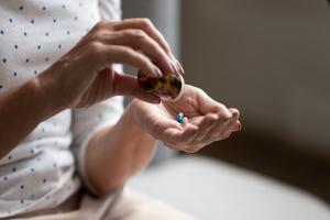 women taking pills for her Cholesterol Screening