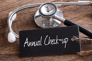 stethoscope on wood with Annual check up word as medical concept